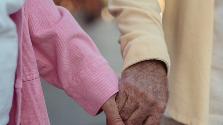 close up shot of an elderly couple holding hands